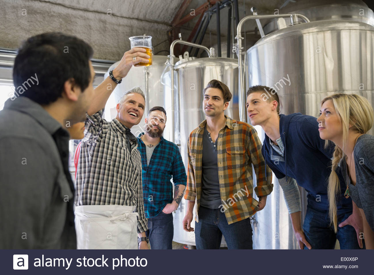 Brewery tour guide showing group beaker of beer - Stock Image