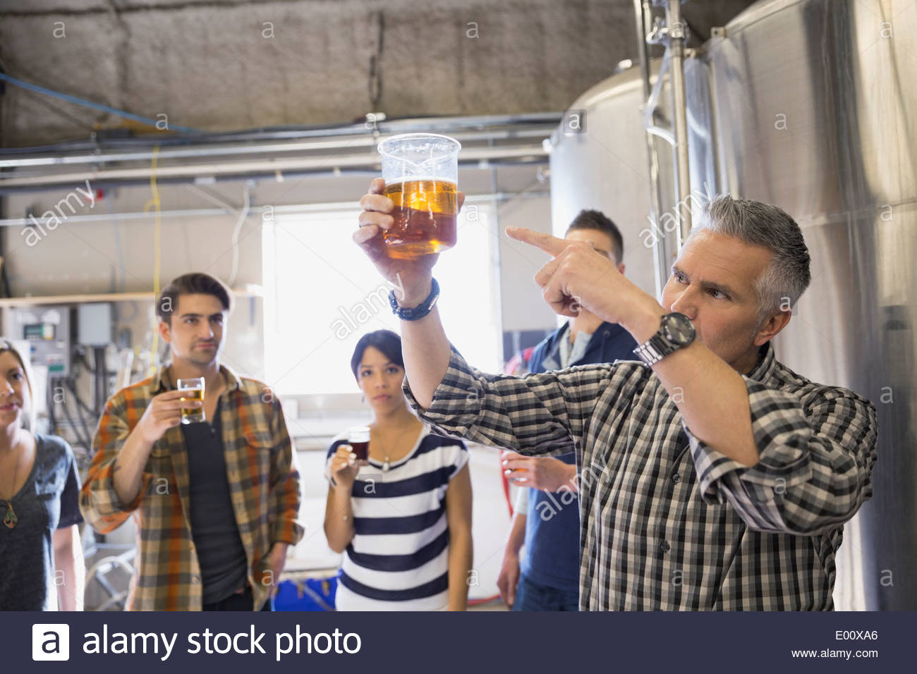 Brewery tour guide pointing to beer in beaker - Stock Image