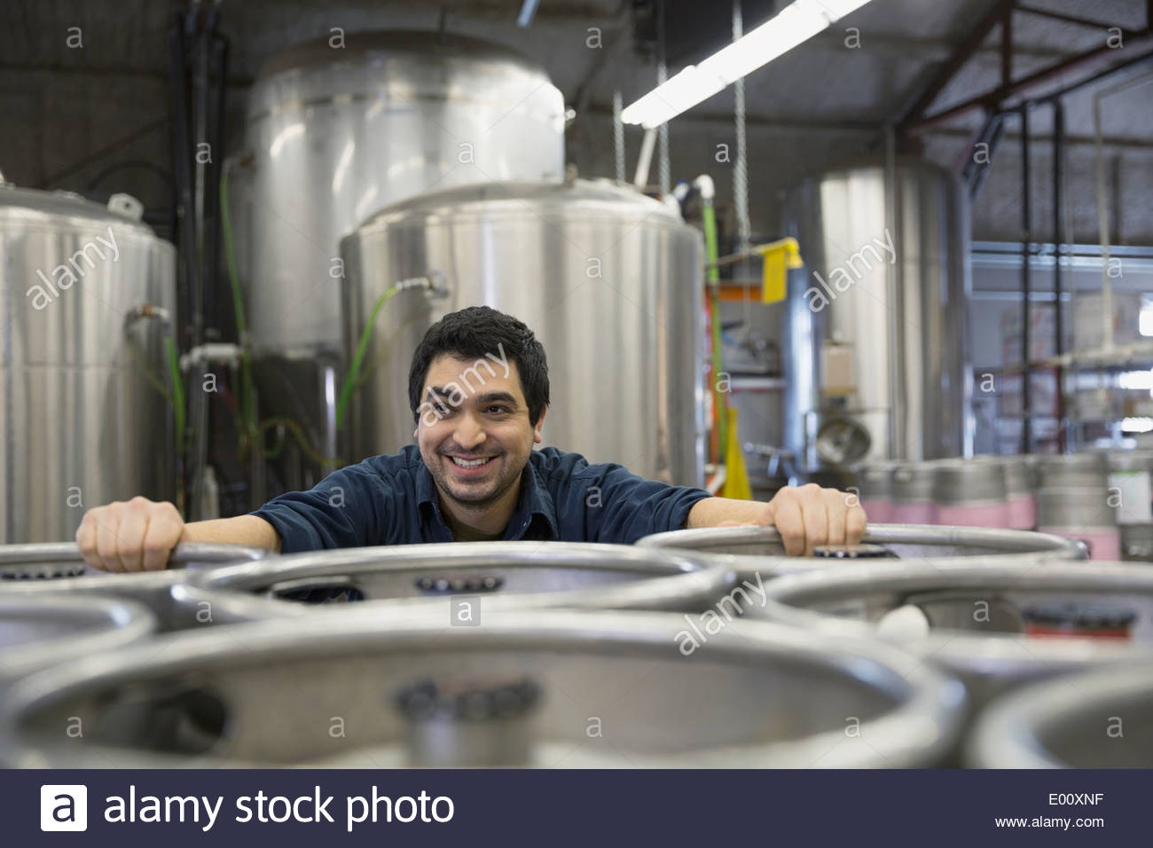 Brewery worker leaning on kegs - Stock Image