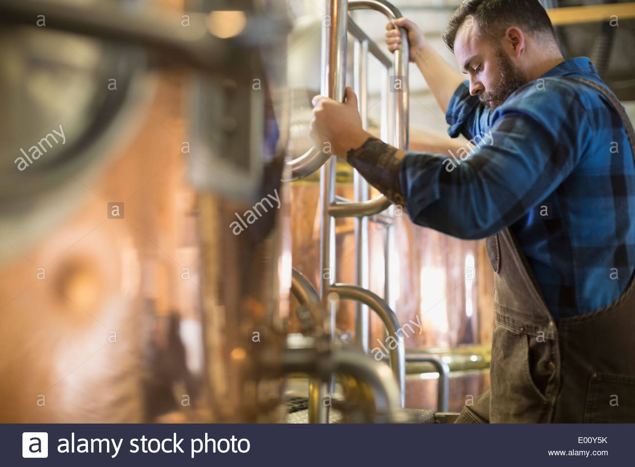 Brewery worker checking copper stills - Stock Image