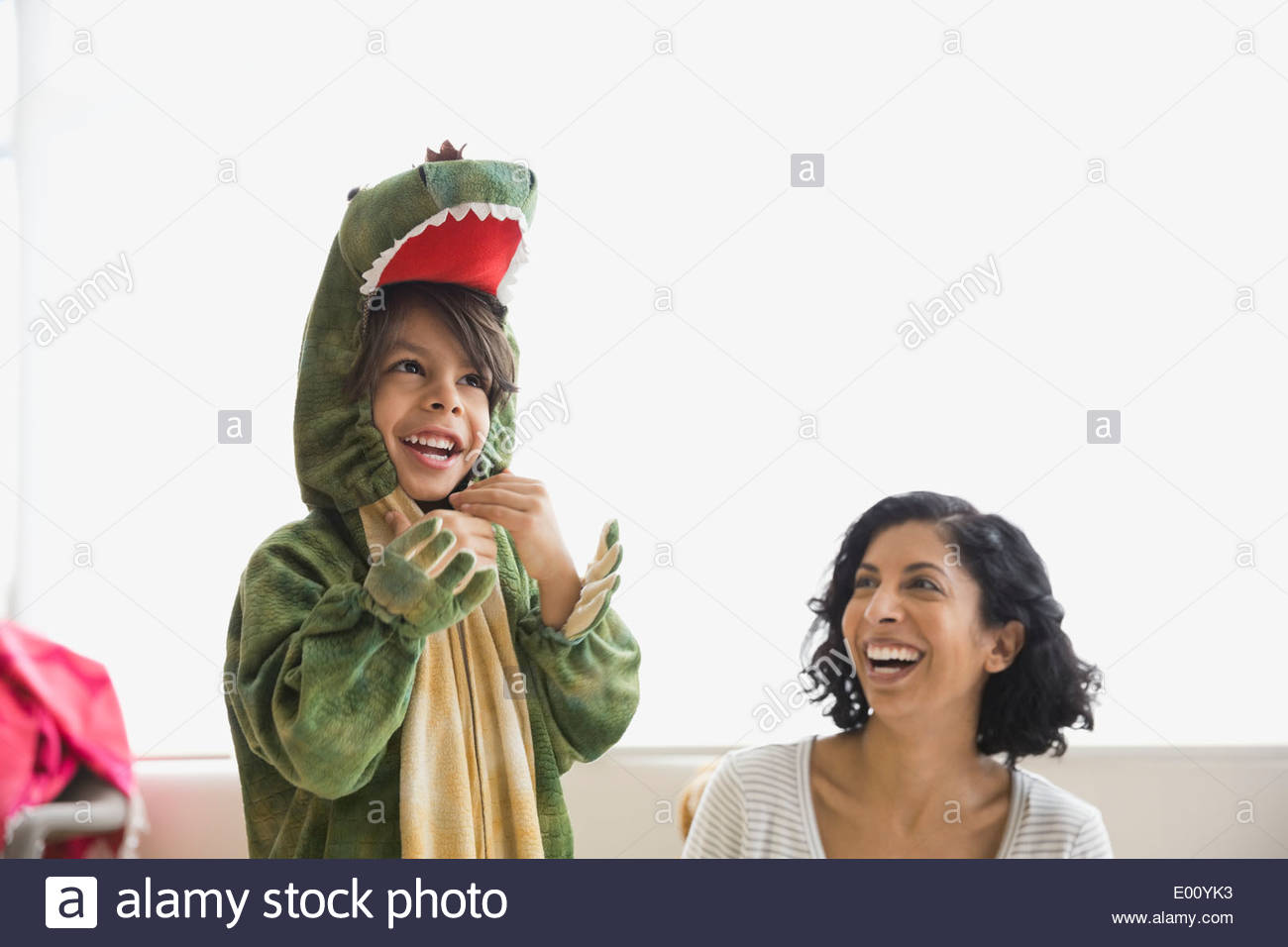 Boy in dragon costume laughing with mother - Stock Image