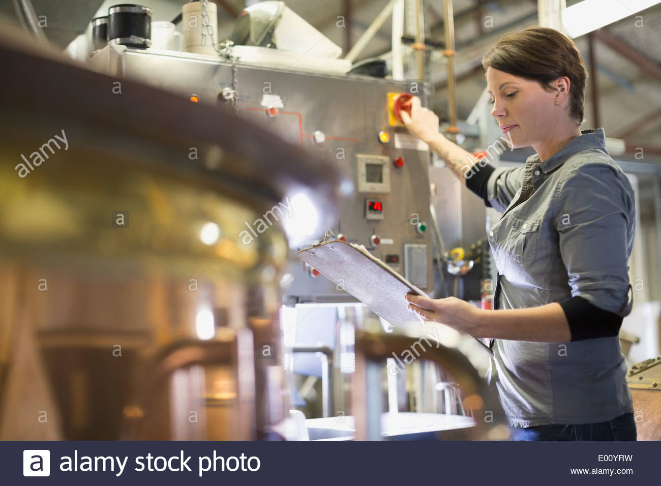 Brewery worker with clipboard operating machinery - Stock Image