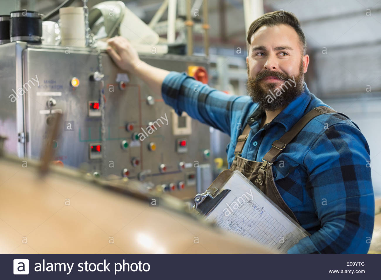 Confident brewery worker at control panel - Stock Image