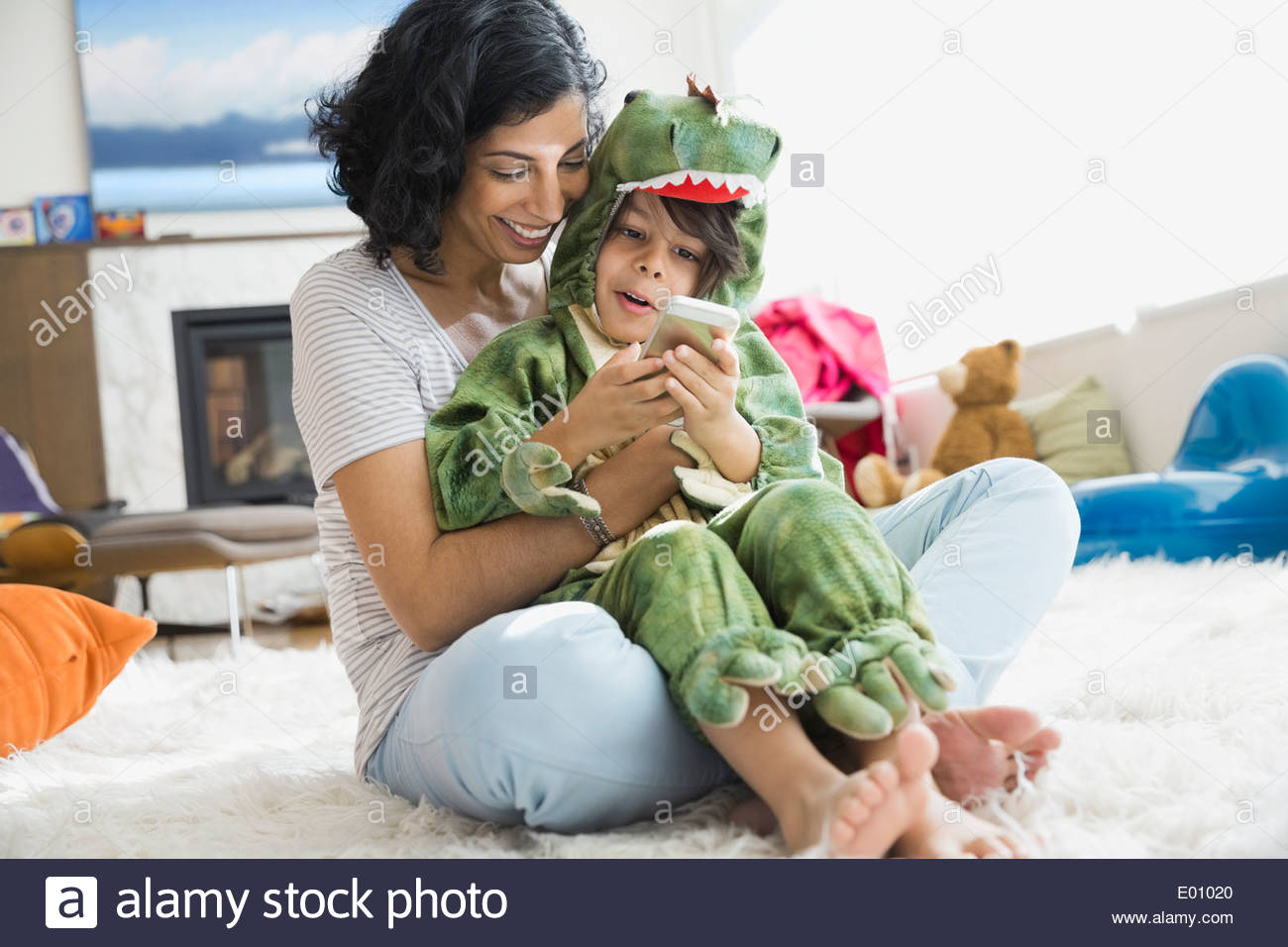 Mother holding son in dragon costume - Stock Image