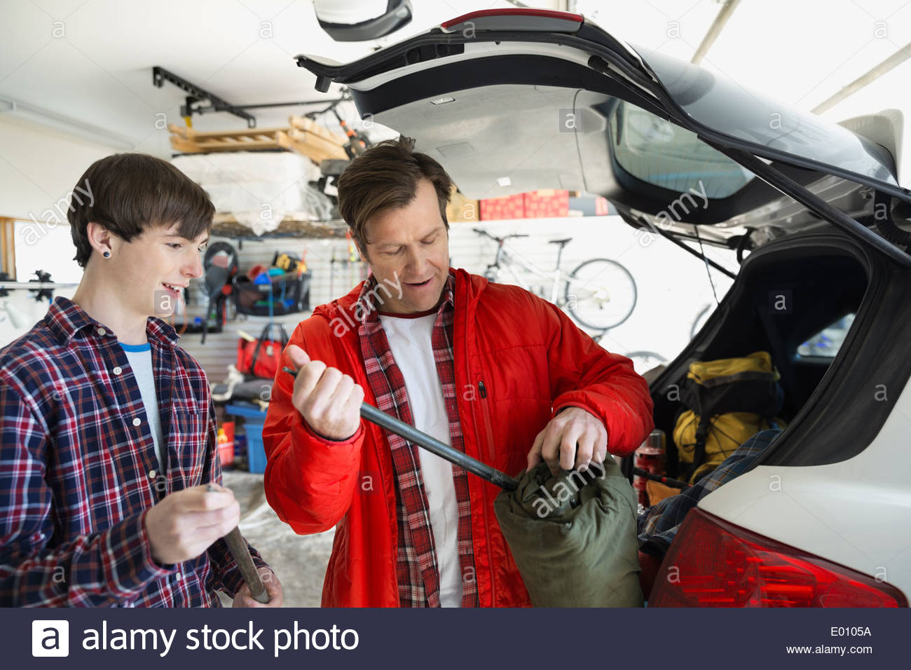Father and son loading camping gear into car - Stock Image