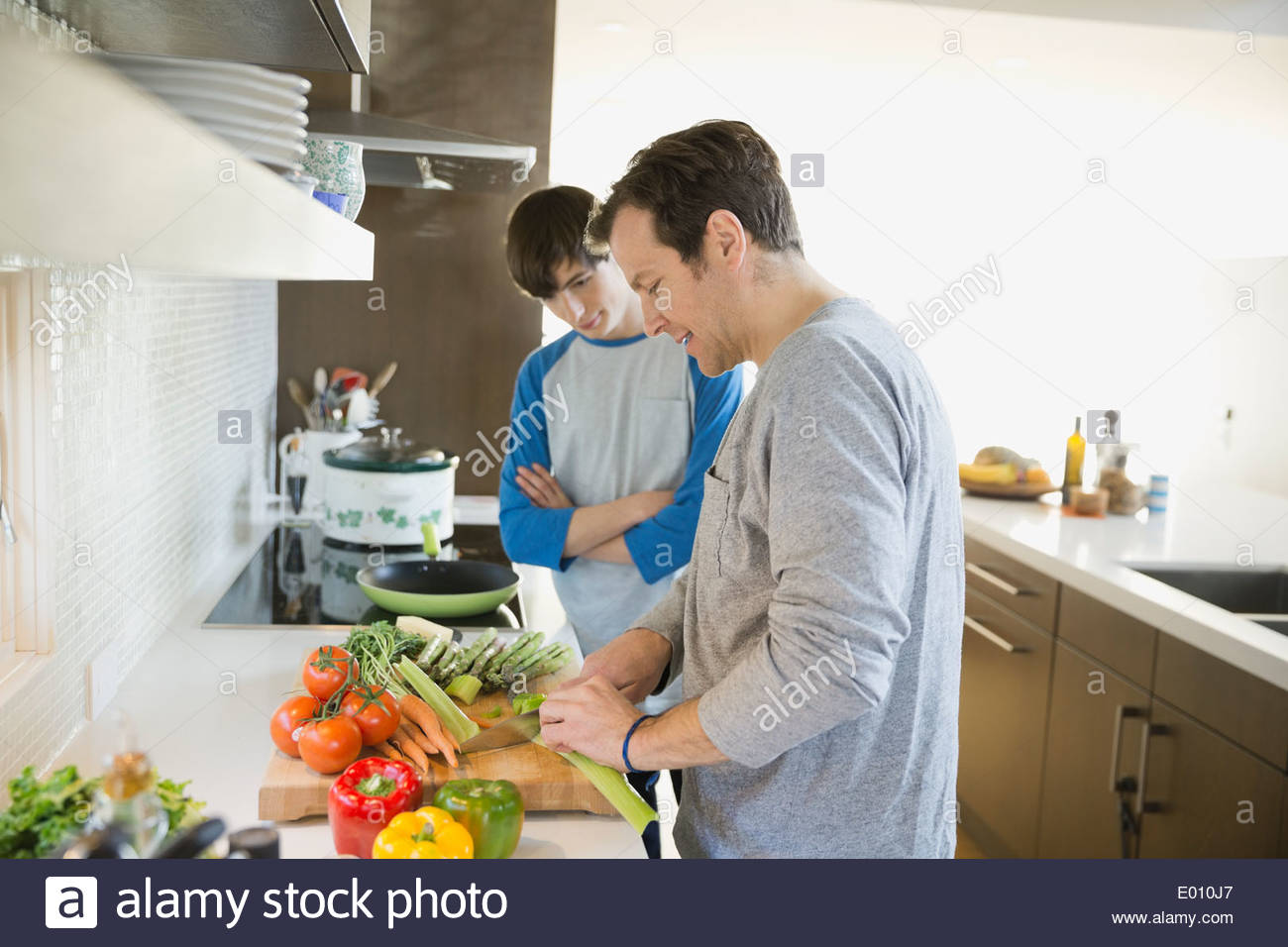 Father teaching son to cook in kitchen - Stock Image