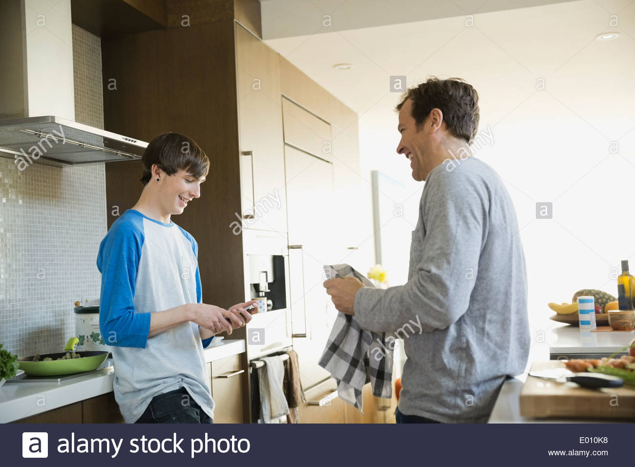 Father and son talking in kitchen - Stock Image