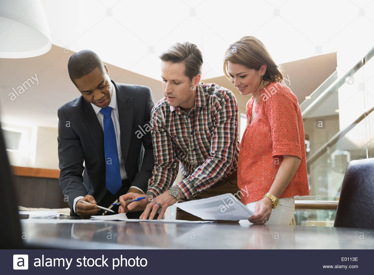 Couple signing documents for financial advisor - Stock Image