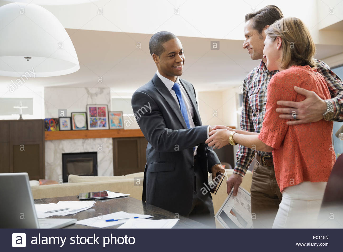 Couple shaking hands with financial advisor - Stock Image