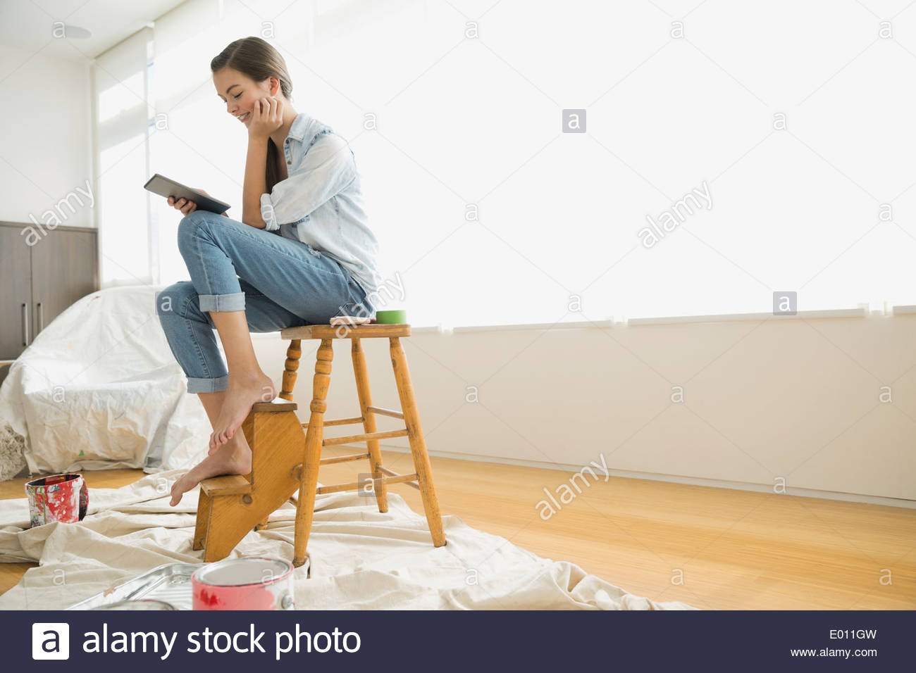 Girl with digital tablet preparing to paint room - Stock Image