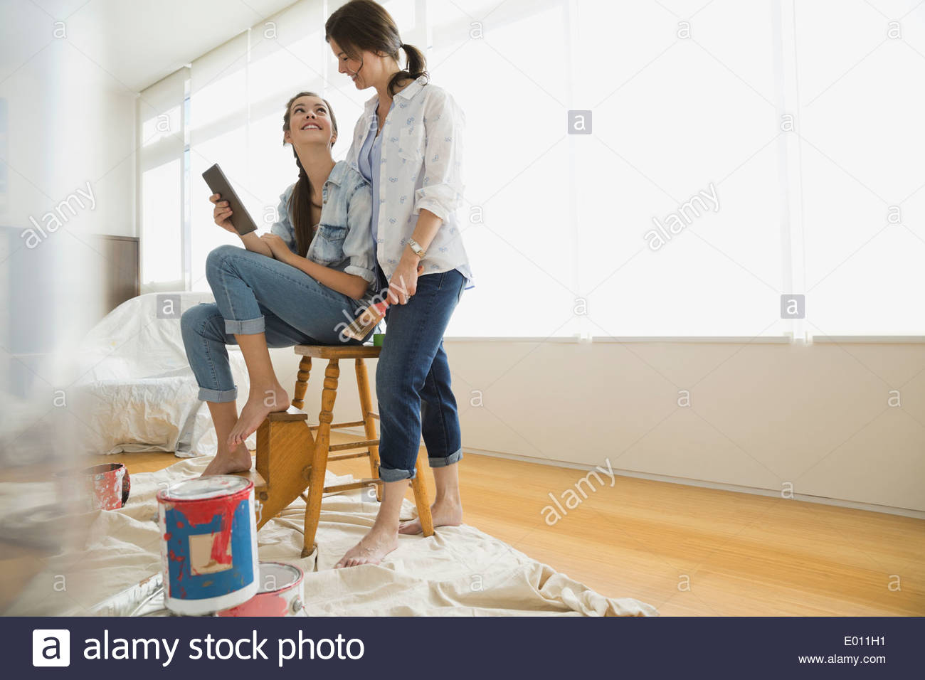 Mother and daughter preparing to paint living room - Stock Image