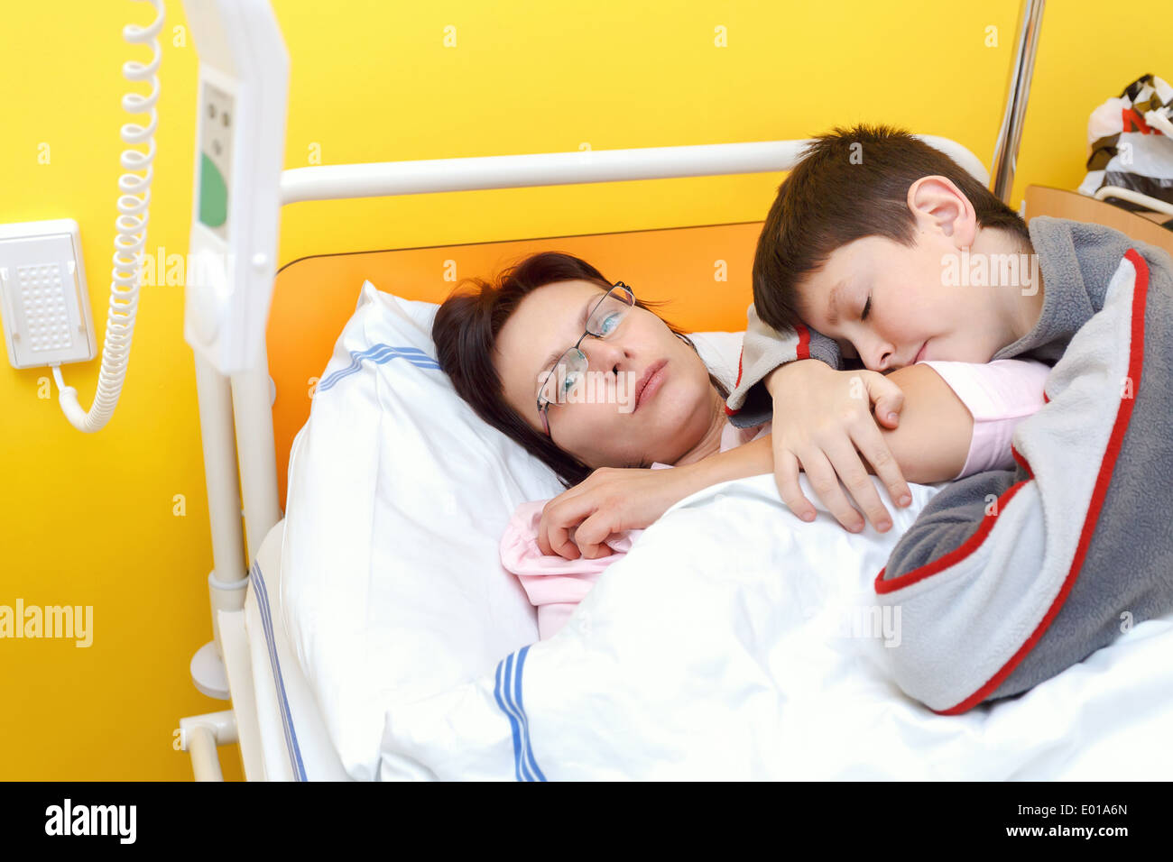 Real people in real situation, sad middle-aged woman lying in hospital with pneumonia, son visit his mother - Stock Image