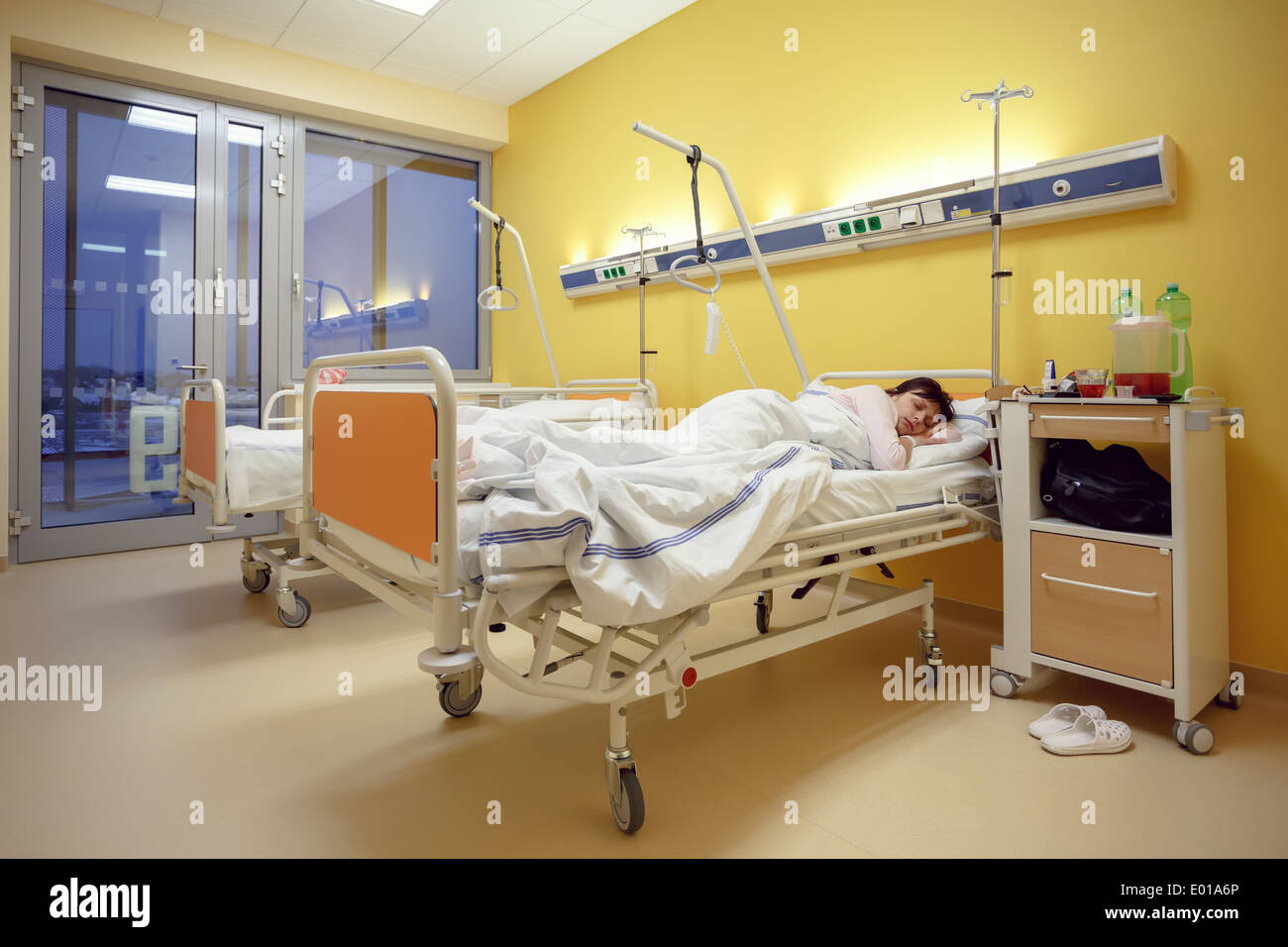 Real people in real situation, sad middle-aged woman lying in hospital with pneumonia - Stock Image