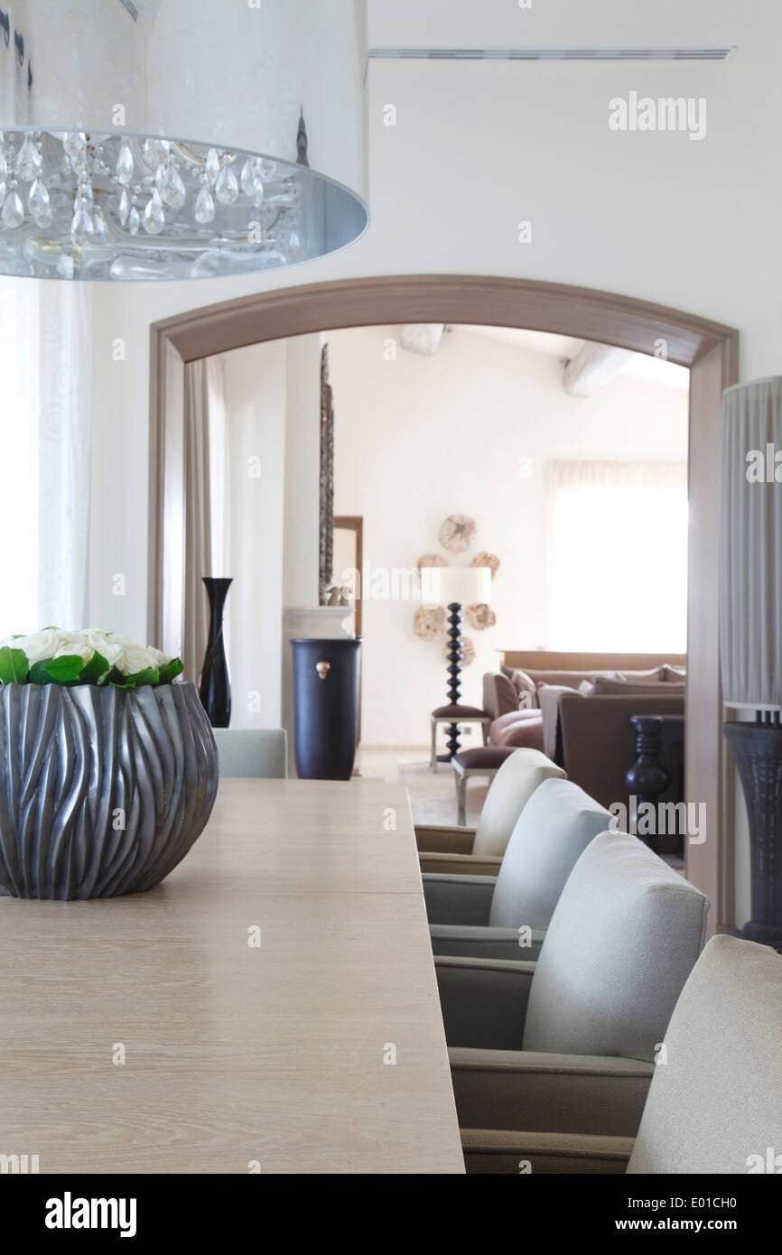 Detail of modern chandelier over dining table and dining chairs in subtly differing pale shades sitting room lies beyond - Stock Image