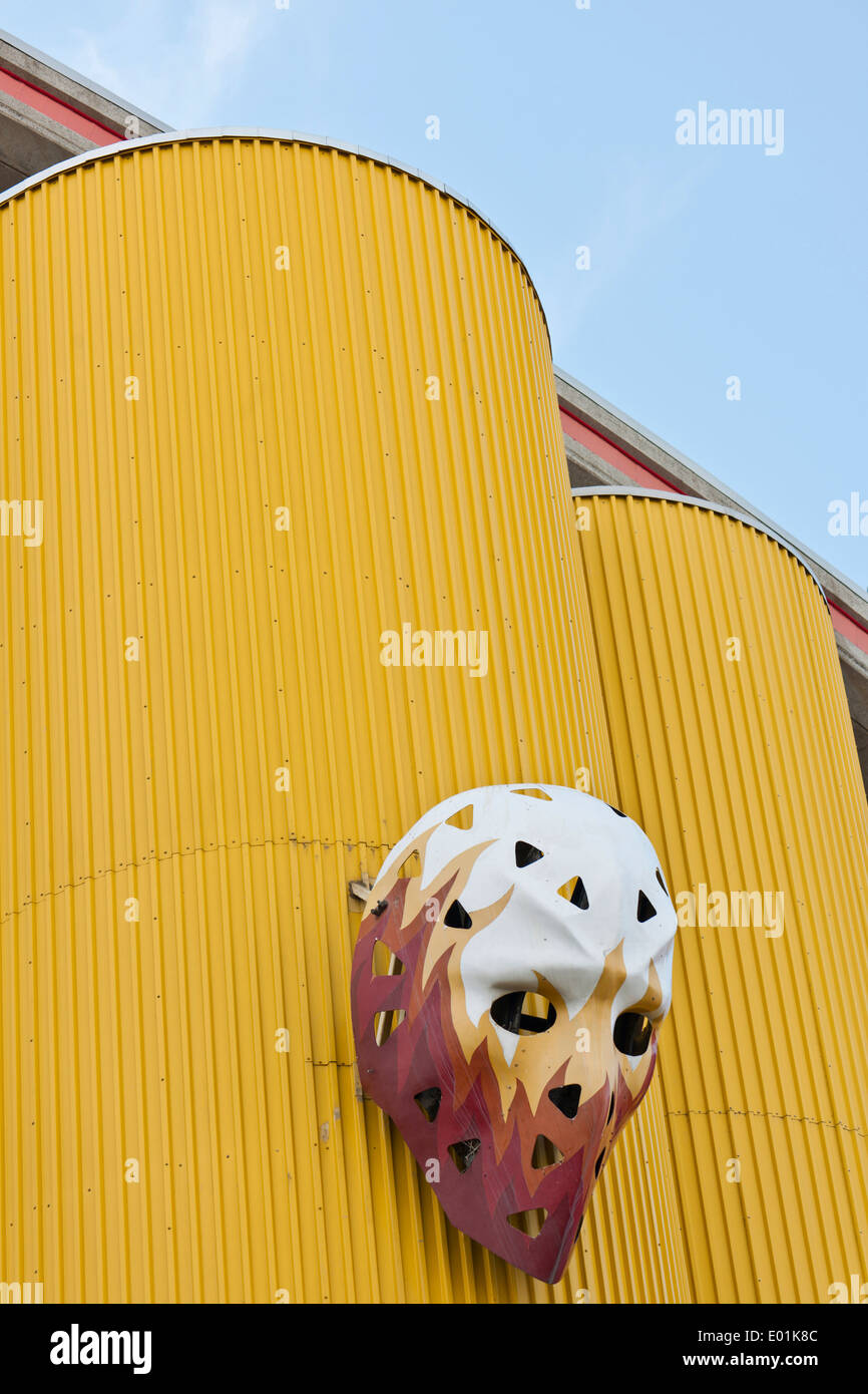 Scotiabank Saddledome. Ice hockey goalkeeper's mask decorated with flames is suspended from a yellow facade. - Stock Image