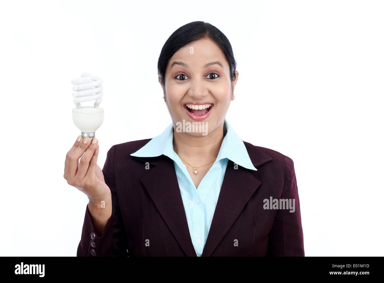 Young Indian business woman holding bulb against white background Stock Photo