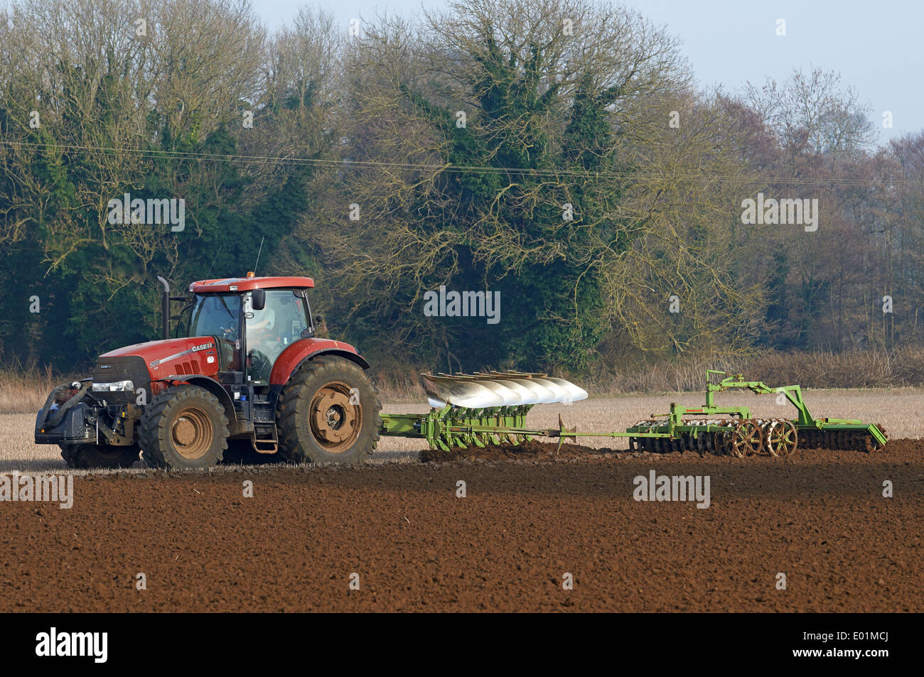 Tractor ploughing with a farrow press attachment - Stock Image