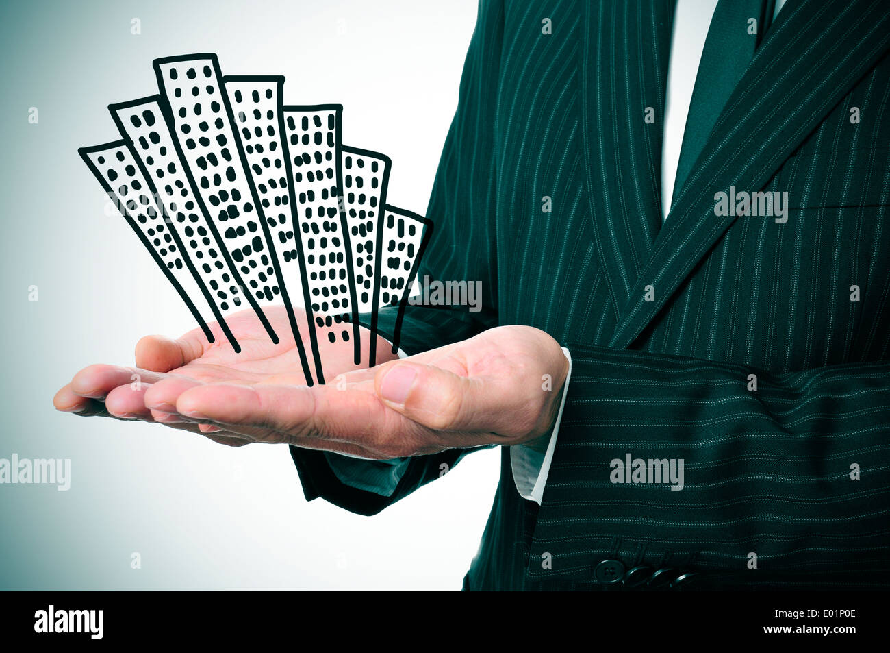 a businessman showing a pile of drawn buildings in his hands - Stock Image