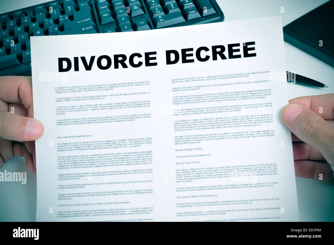 closeup of man hands holding a divorce decree on a desk - Stock Image