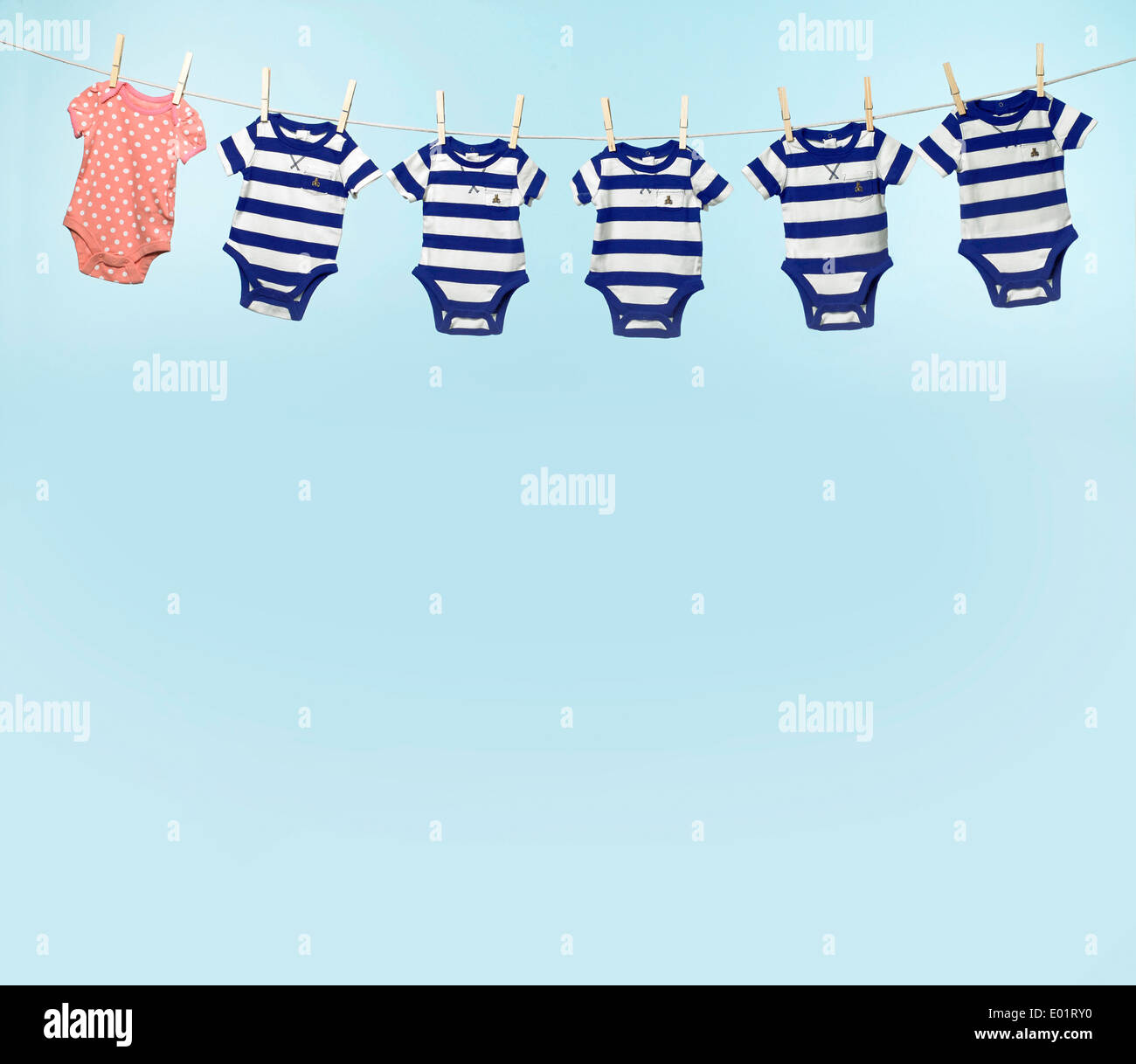Baby light blue background with 6 baby clothes - Stock Image