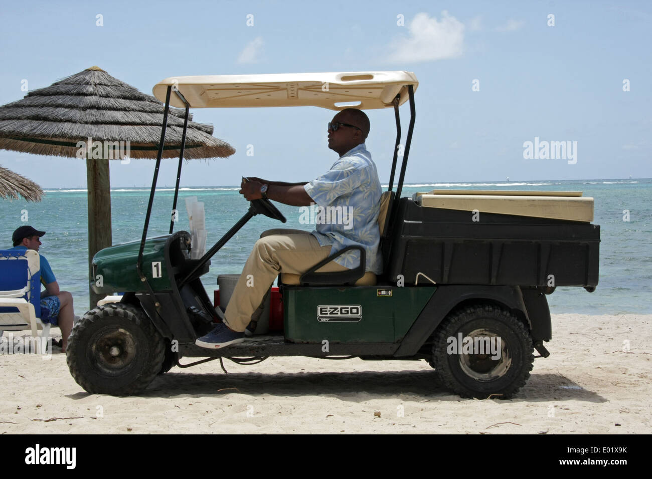 a drinks cart (golf buggy) appears on Coco beach to serve ice cold drinks to sunbathers, St James Club, Antigua - Stock Image