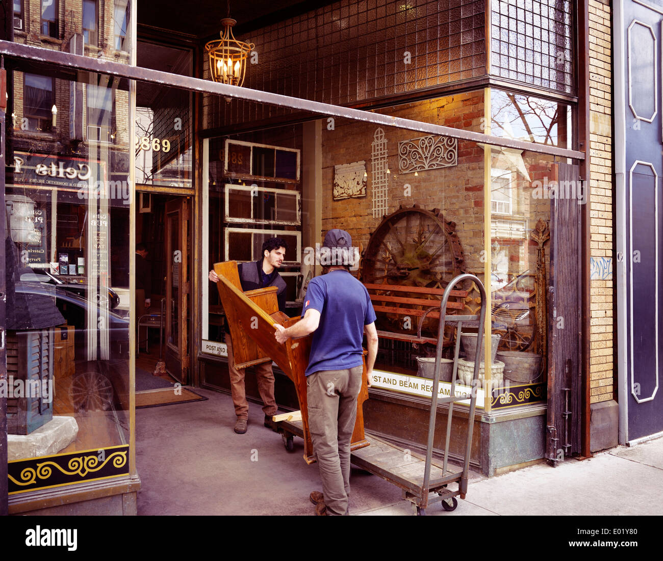 Workers delivering furniture to Post and Beam Reclamation, antique home decor store at the Junction neighbourhood in Toronto - Stock Image