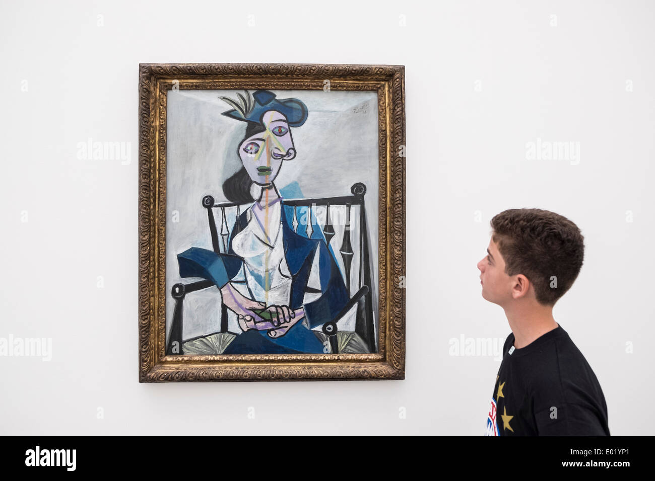 Boy looking at painting by Pablo Picasso ' Sitzende Frau, 1941' at Pinakothek Museum in Munich Germany - Stock Image