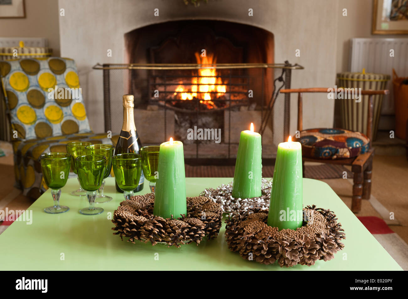 Green candles in cone candle holders on green tabletop with green glassware - Stock Image