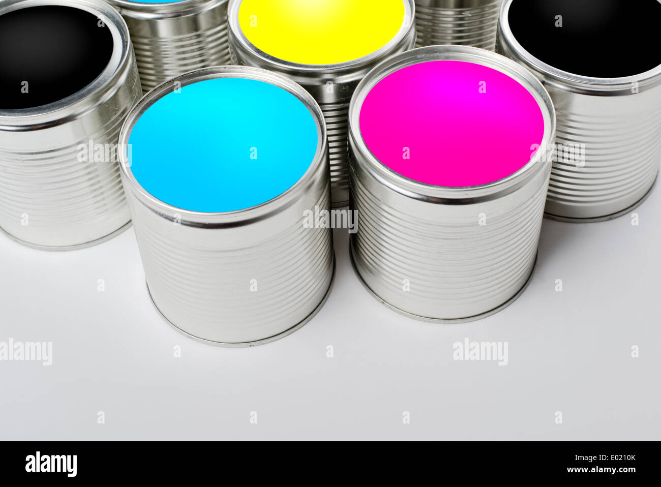 CMYK color paint tin cans opened top view. Cyan, Magenta, Yellow and Black colors are basic for printing industry. - Stock Image