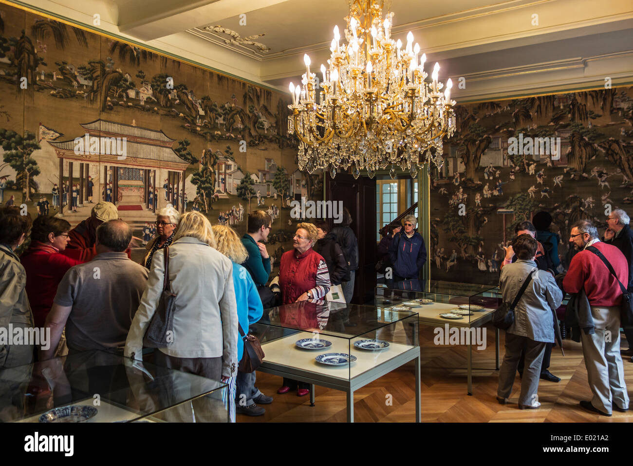Tourists visiting the 18th century silk wallcovering in the Chinese salon at Museum Arnold Vander Haeghen in Ghent, Belgium - Stock Image