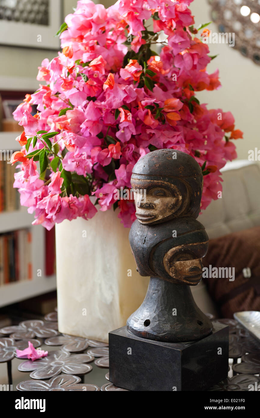 Pink flowers and carved sculpture on side table in Baja home - Stock Image