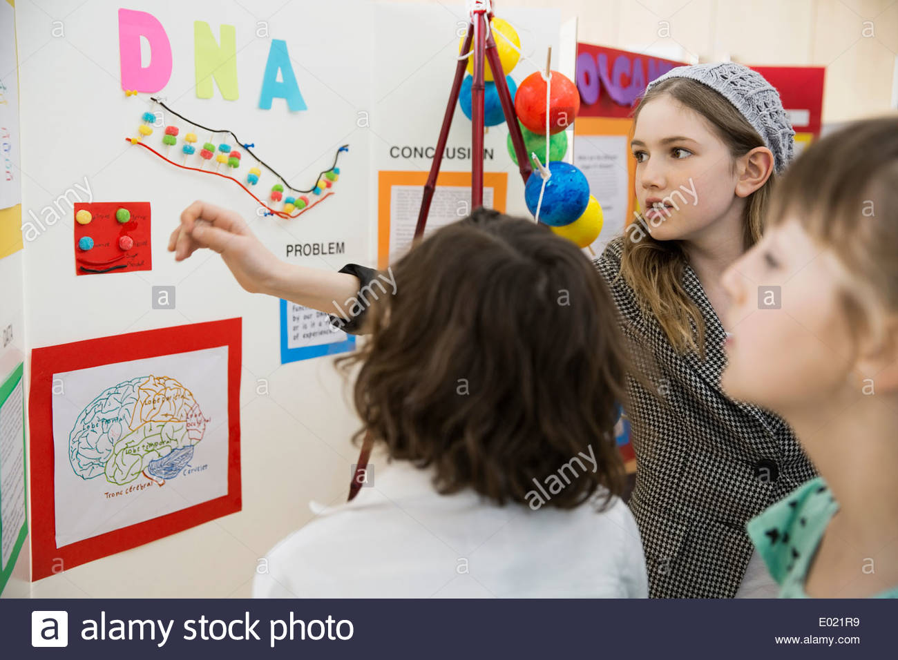 School girl explaining science fair project to classmates - Stock Image