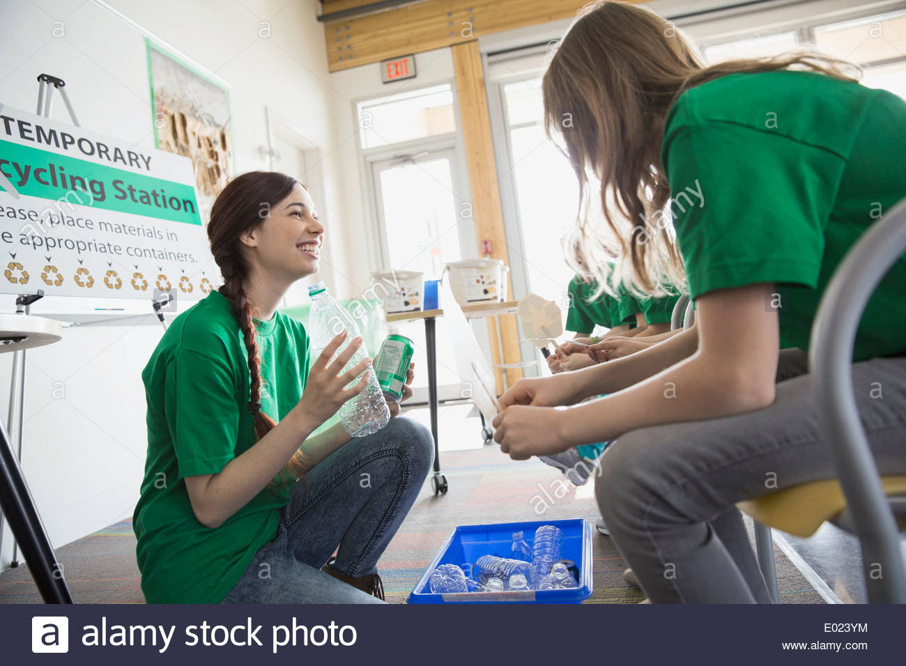 Mentor teaching students to recycle in classroom - Stock Image