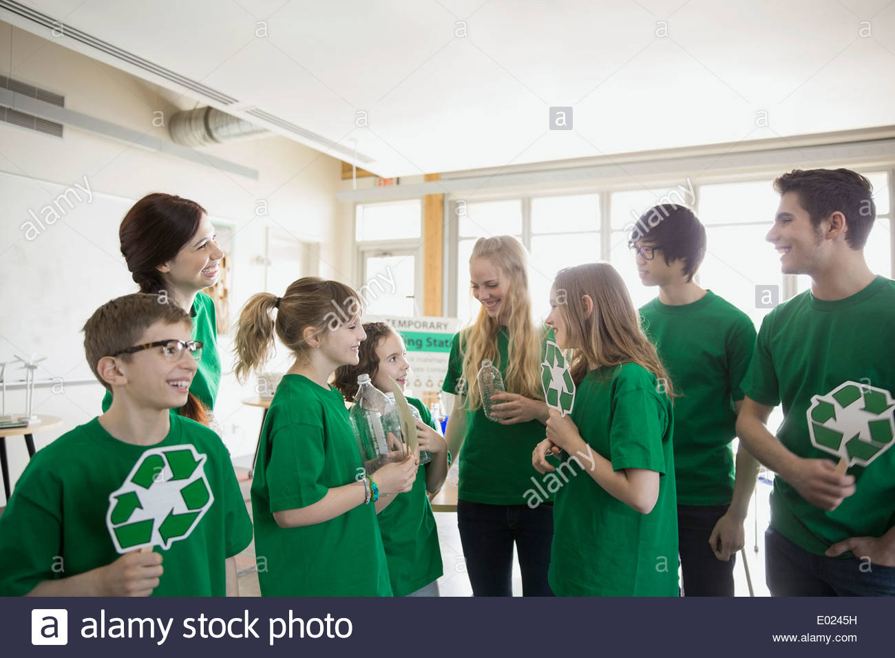 Mentors and students with recycle symbols in classroom - Stock Image