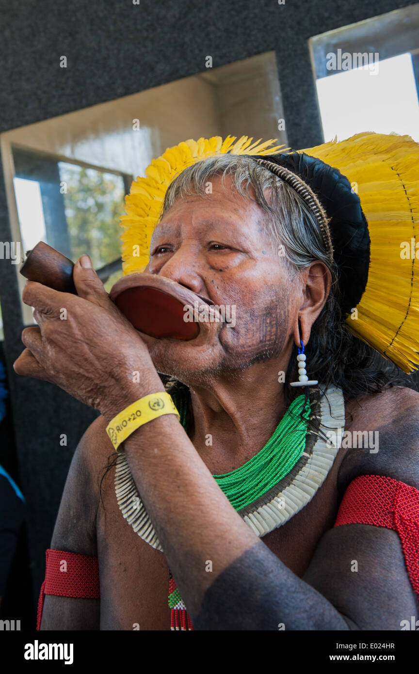 Kayapo Chief Raoni Txucarrhamae smokes his pipe, with headress and 'Rio+20' yellow wrist band for participants. The People's Summit at the United Nations Conference on Sustainable Development, Rio de Janeiro, Brazil. - Stock Image