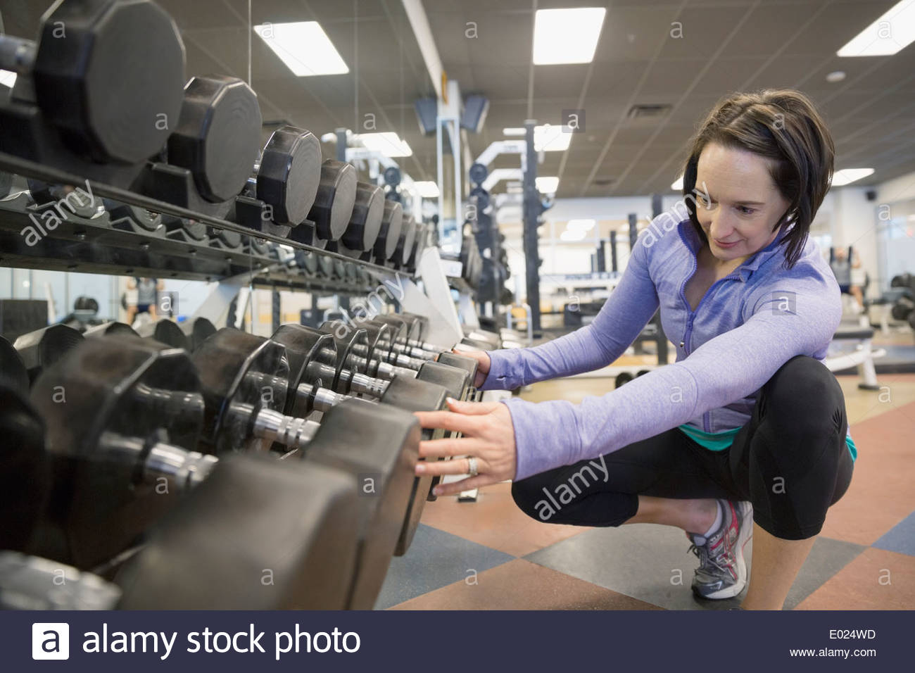 Woman looking at dumbbells on rack at gym - Stock Image