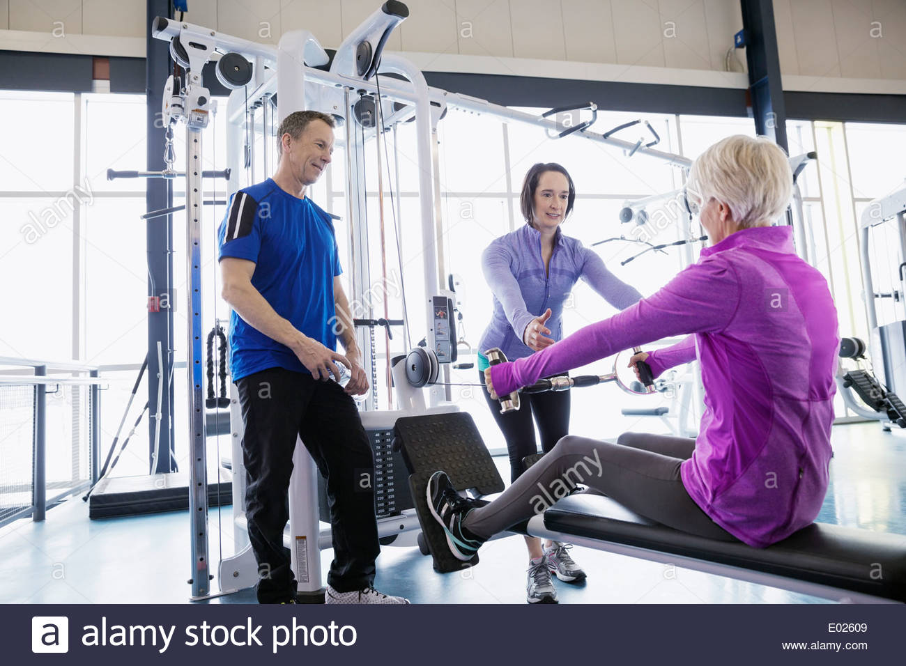 People using weight machines at gym - Stock Image