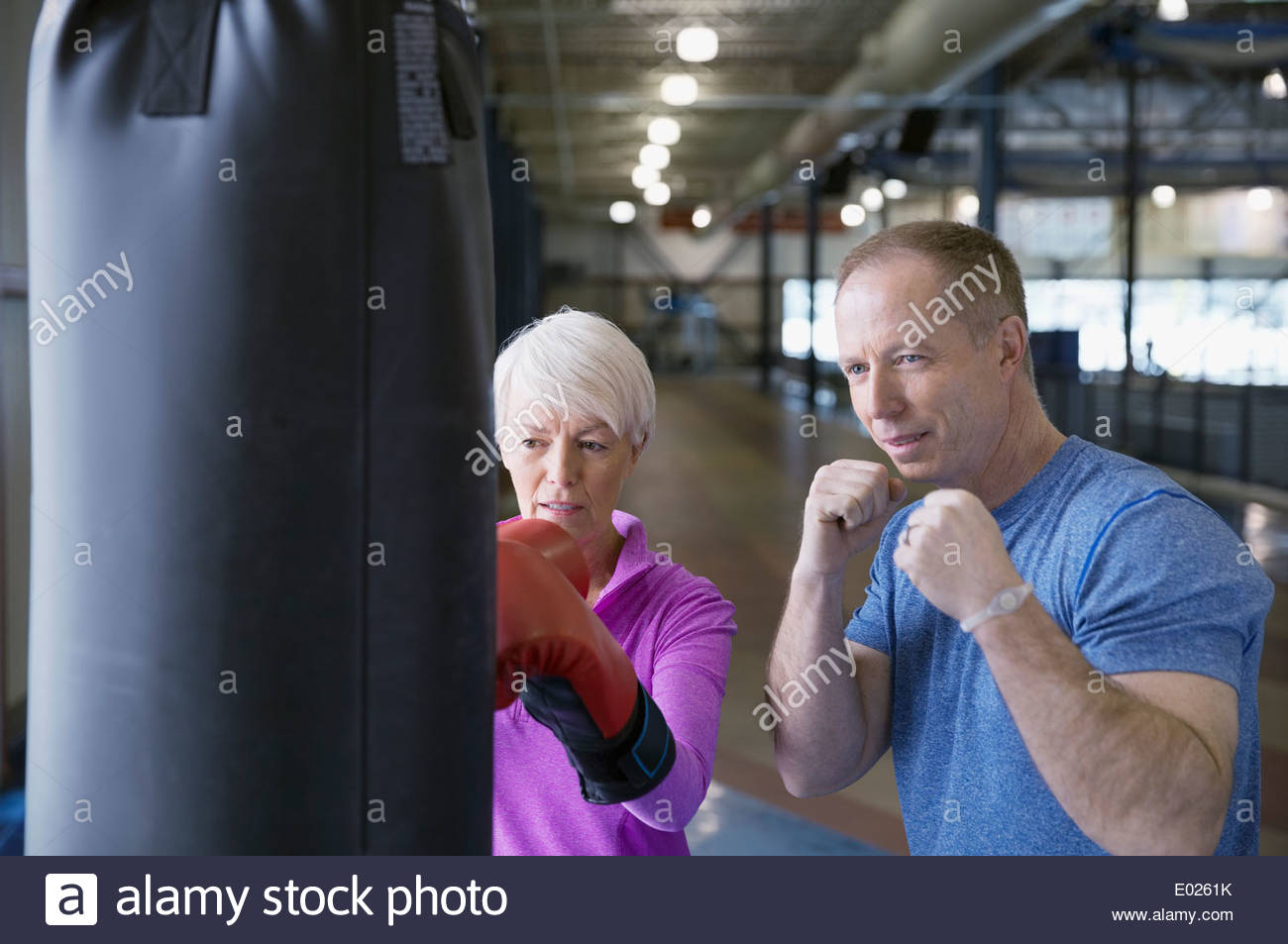 Woman boxing with personal trainer at gym - Stock Image