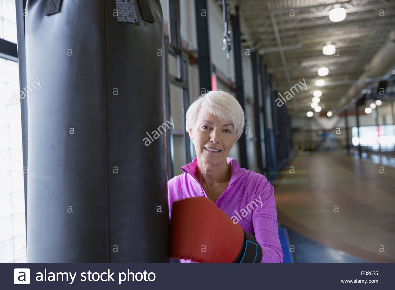Portrait of smiling woman boxing at gym - Stock Image