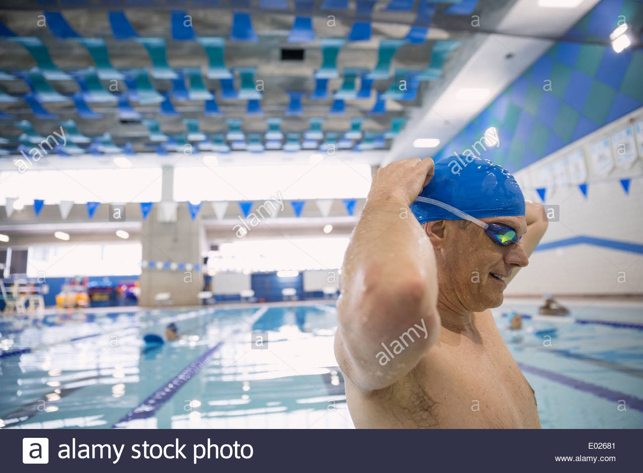 Man putting on goggles at indoor swimming pool - Stock Image