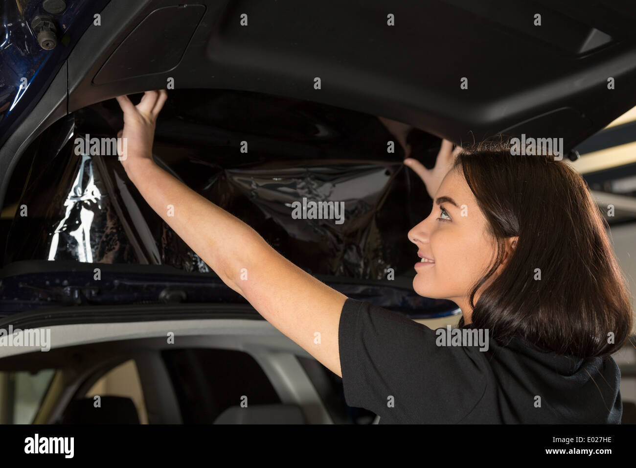 Car wrapping specialist attaching tinting foil to car window Stock Photo