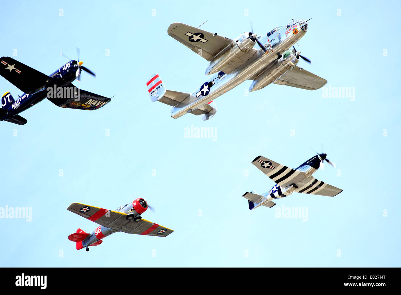 Four world war 2 airplanes in formation; a B-25 bomber, a mustang, a corsair and an SNJ T6 Texan - Stock Image