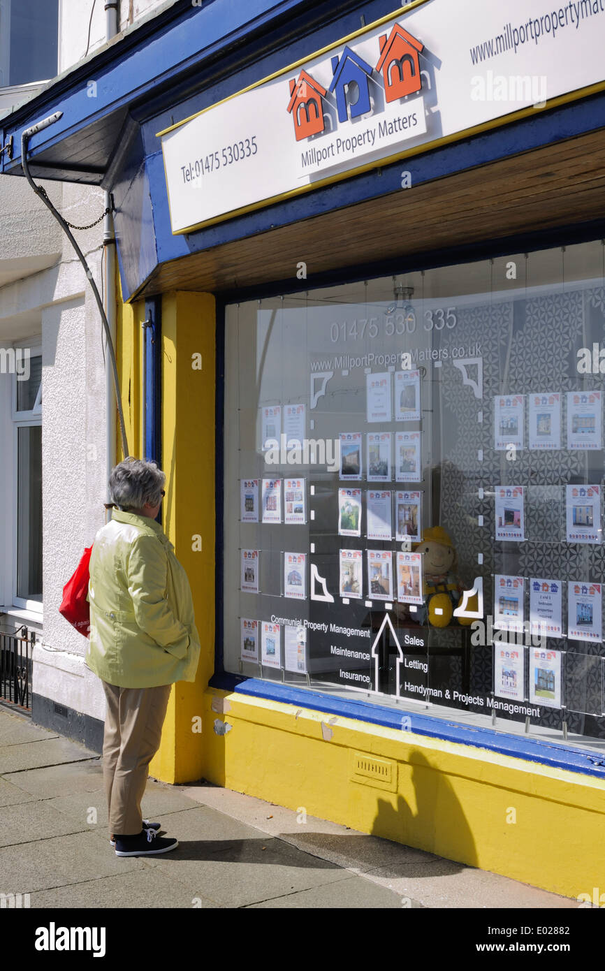 A senior woman browses property for sale on the holiday Island of Cumbrae - Stock Image