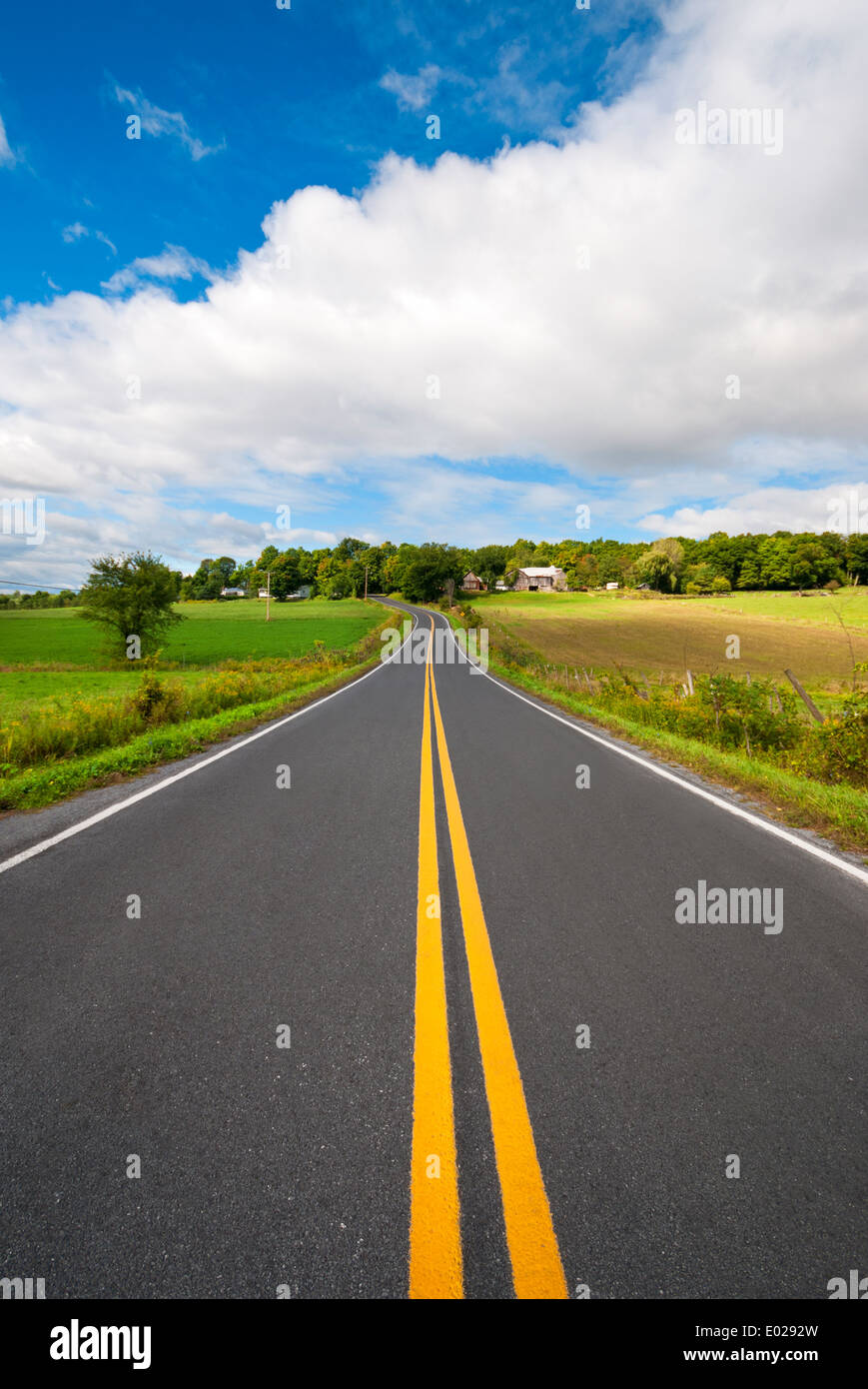 A country road leading off into the distance. - Stock Image