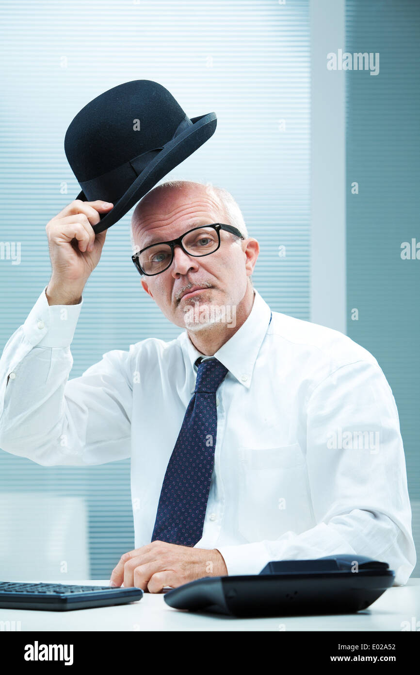 Elegant English businessman with square glasses greeting with his bowler - Stock Image