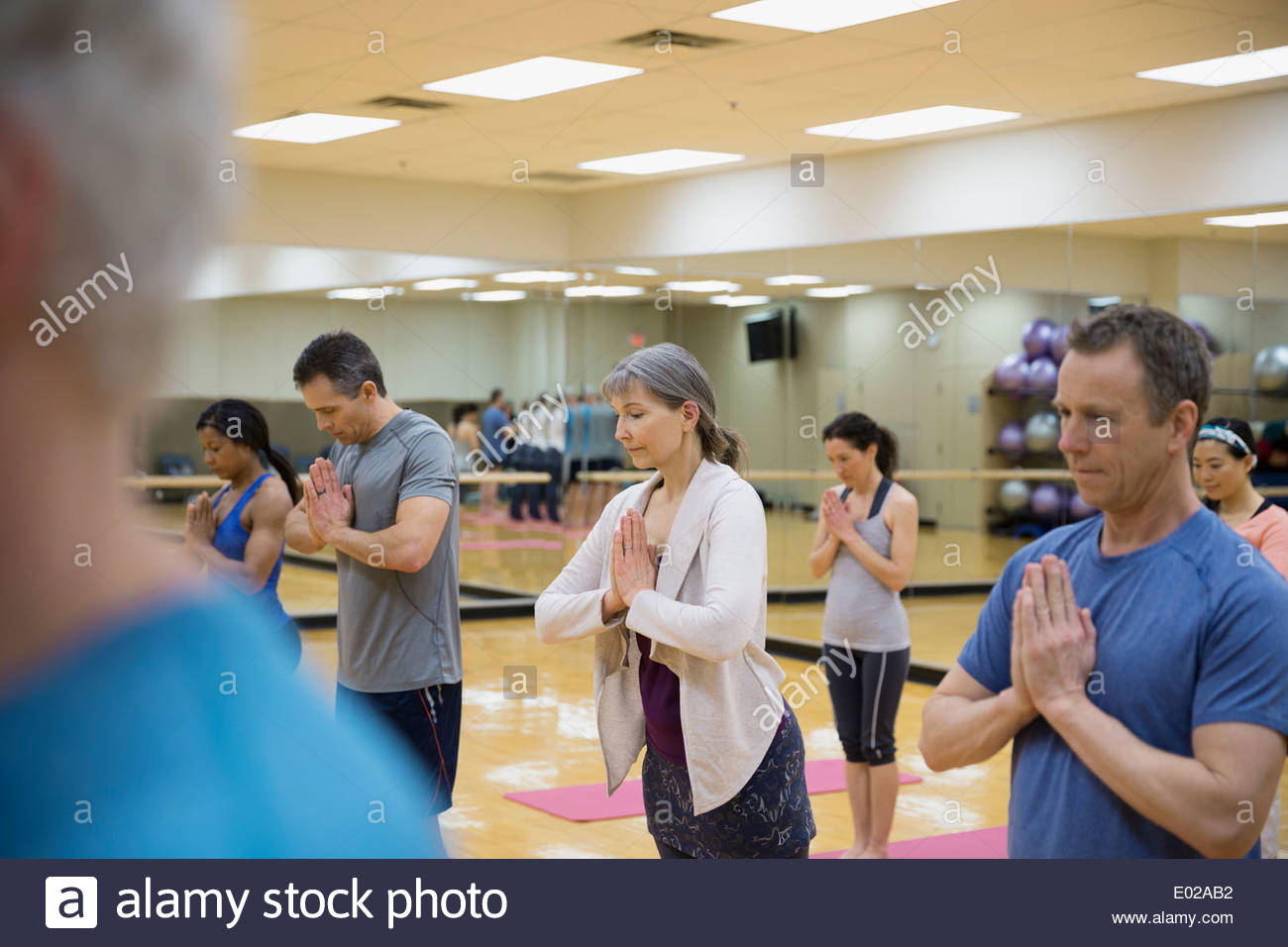 Group practicing prayer pose in yoga class - Stock Image