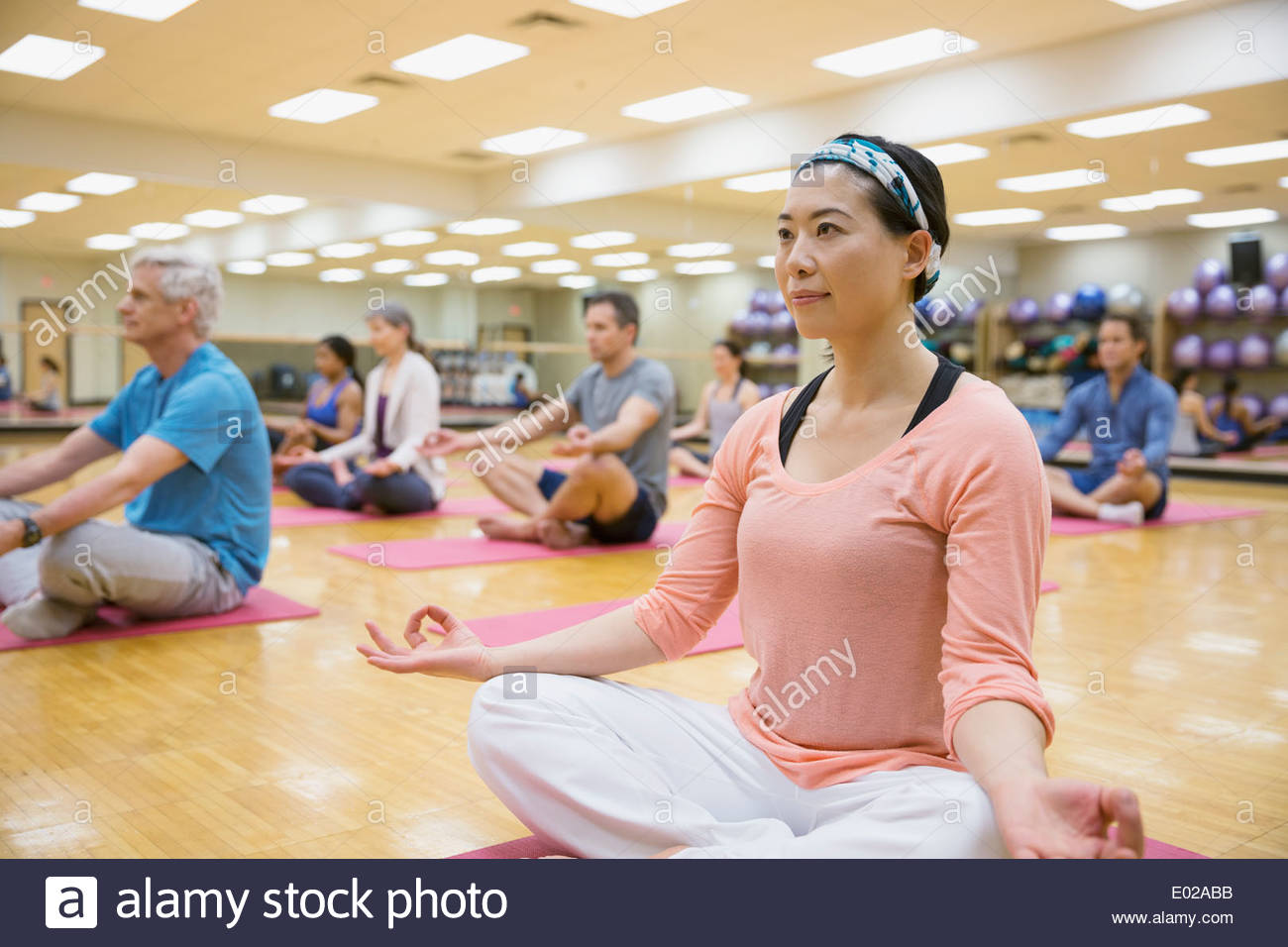 Group in lotus position in yoga class - Stock Image