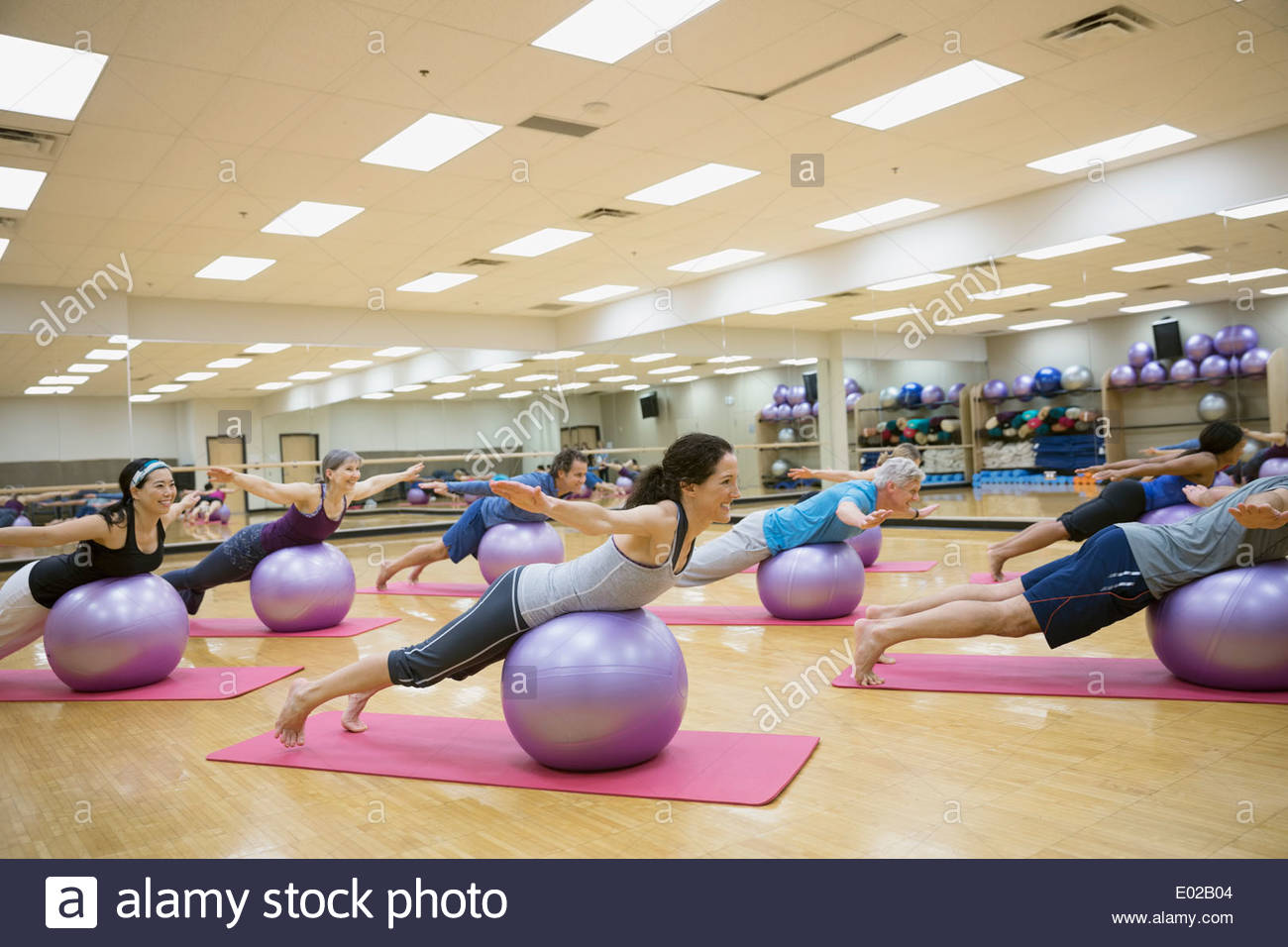 Group balancing on fitness balls in exercise class - Stock Image