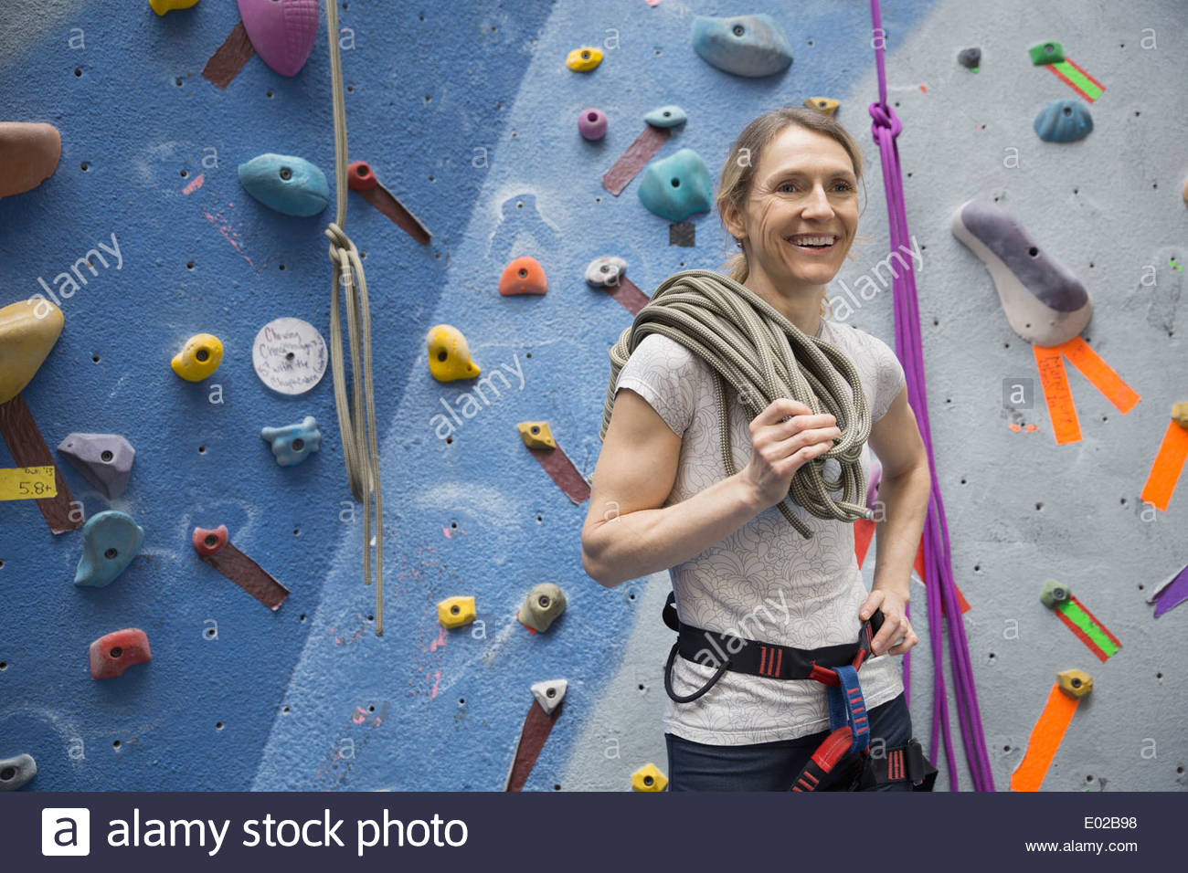Smiling woman holding rope at rock climbing wall - Stock Image