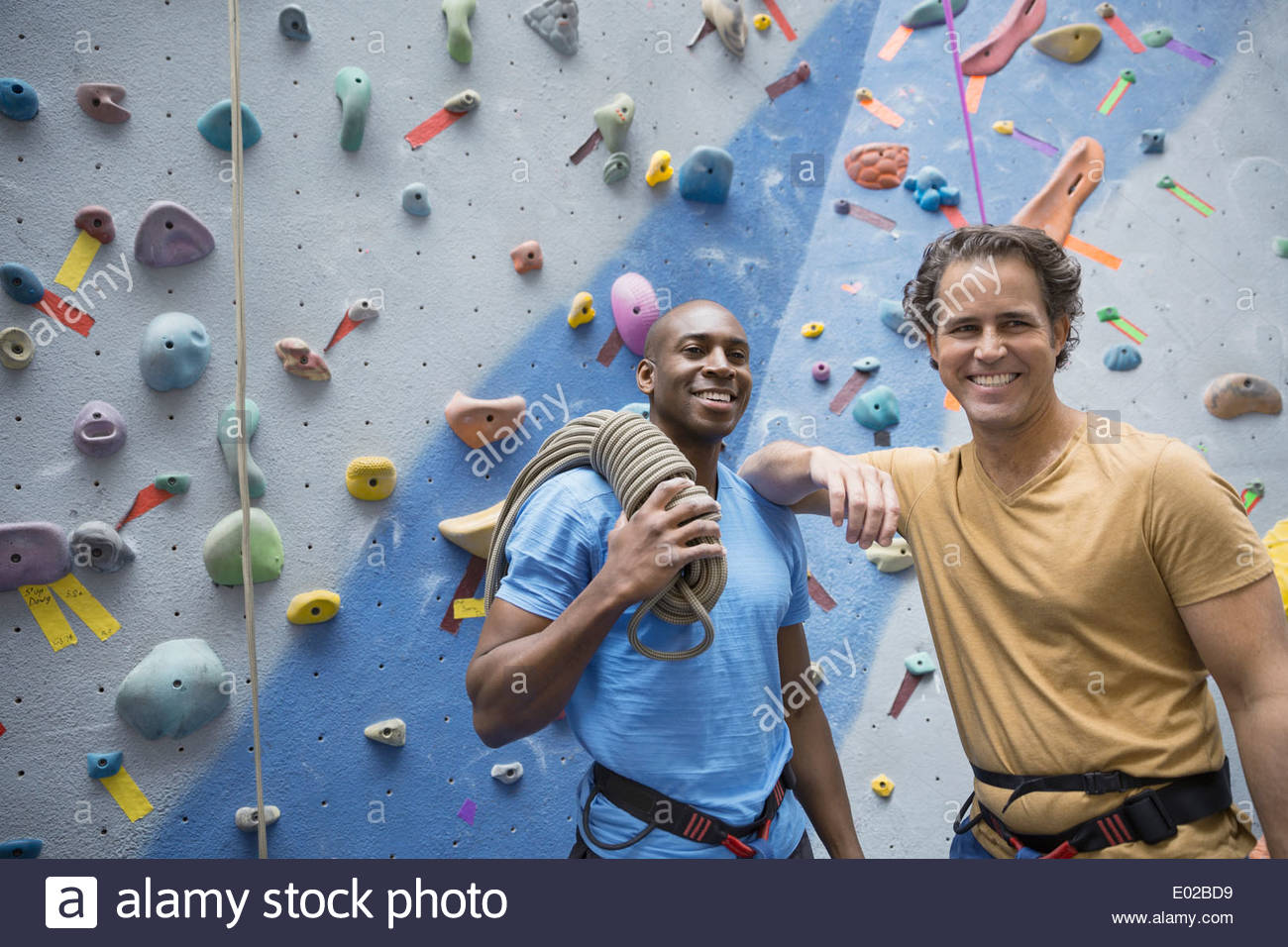 Smiling men with rope at rock climbing wall - Stock Image